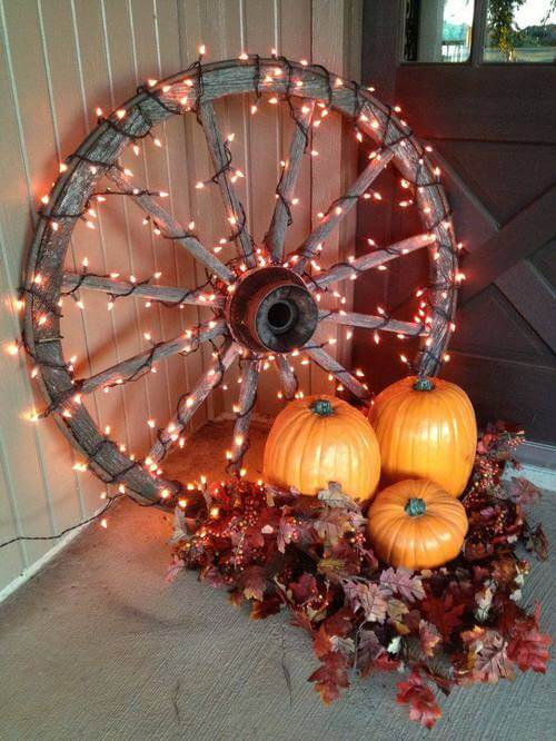 A lit up wheel of fall decor for the deck