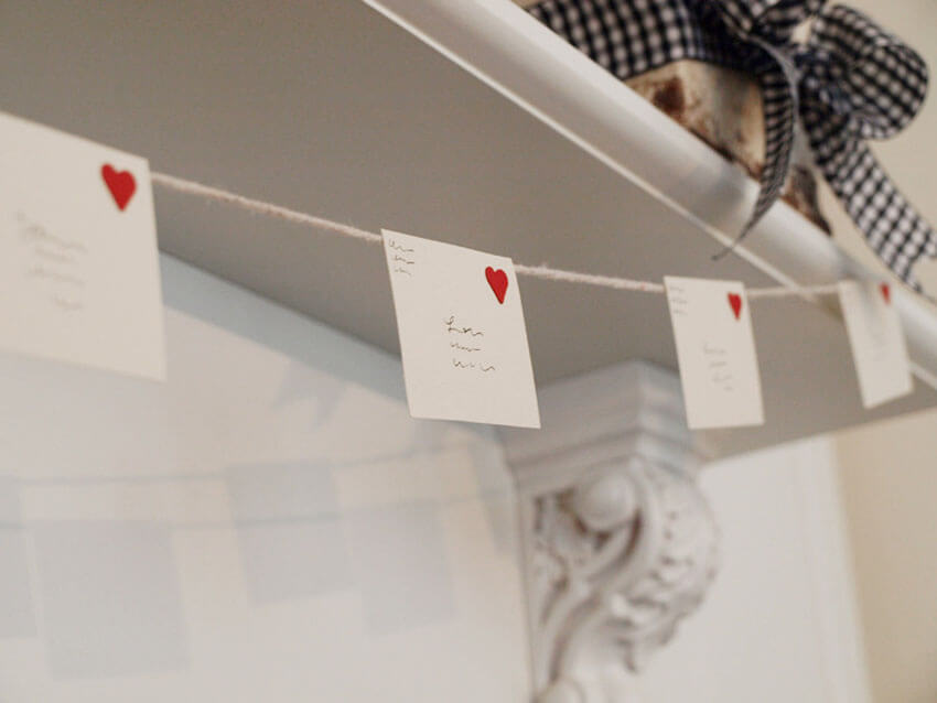 Hang love letters as garland to decorate for Valentine's Day.
